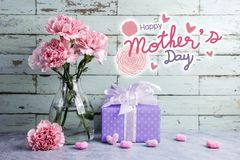 Happy mothers day message on wood background and pink carnation. Flower in clear bottle and gift box stock images