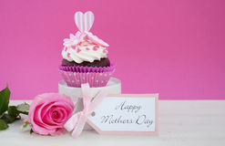 Happy Mothers Day pink and white cupcake. Happy Mothers Day pink and white cupcake on retro style cake stand and pink rose on vintage white wood table, with Royalty Free Stock Photos