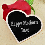 Happy mothers day. A rose and the sentence happy mothers day written in a heart-shaped chalkboard Stock Photos
