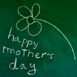 Happy mothers day. The sentence happy mothers day handwritten with chalk in a chalkboard, with a drawing of a flower Stock Photos