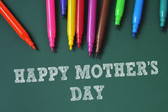 Happy mothers day. Sentence happy mothers day written in a green chalkboard and some felt-tip pens of different colors Royalty Free Stock Photos