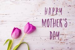Happy mothers day sign and flowers composition. Studio shot. Royalty Free Stock Photography