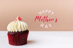 Happy Mothers Day, sweet red heart on white cream cupcake royalty free stock image