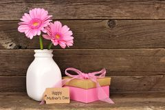 Happy Mothers Day tag with gift and pink flowers against rustic wood. Happy Mothers Day tag with gift box and vase of pink flowers against a rustic wood Royalty Free Stock Photos