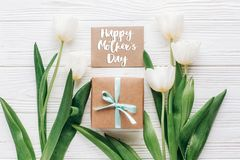happy mothers day text sign on greeting card with stylish present box and tulips on white wooden rustic background. flat lay mock royalty free stock images