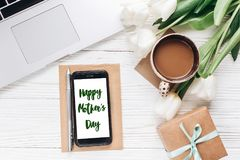 Happy mothers day text sign on phone screen and laptop with morn stock images