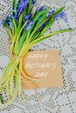 Happy mothers day text sign on stylish craft greeting card and scilla siberica on white rustic tablecloth. stock photography