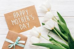 happy mothers day text sign on stylish craft present with greeting card and tulips on white wooden rustic background. flat lay wi