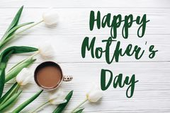 Happy mothers day text sign on tulips and coffee on white wooden. Rustic background. stylish flat lay with flowers and drink with space for text. greeting card royalty free stock photos