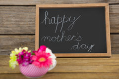 Happy mothers day text written on chalk board with cup of flowers Stock Photos