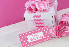 Happy Mothers Day white gift box with pink stripe ribbon. Royalty Free Stock Photo
