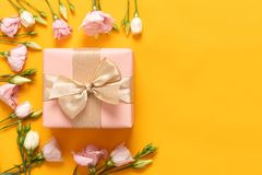 Happy Mothers Day, Womens Day, Valentines Day or Birthday Yellow and Pastel Pink Colored Background. Flat lay with gift box. royalty free stock image
