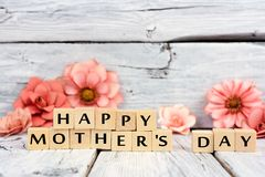 Happy Mothers Day wooden blocks with flowers over white wood Stock Photo