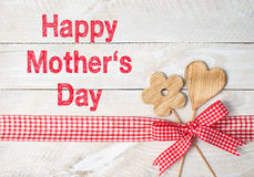 Happy Mothers Day. A wooden heart and a flower with a plaid ribbon and the text Happy Mother's Day on a wooden background stock photography