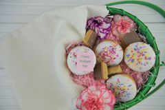 Happy mothers day words on a note in a basket of homemade cakes and fresh flowers. A basket filled with homemade and baked little cakes or cupcakes with white Royalty Free Stock Images