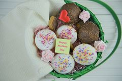 Happy mothers day words on a note in a basket of homemade cakes and fresh flowers. A basket filled with homemade and baked little vanilla and chocolate cakes or Royalty Free Stock Image