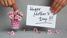 Happy mothers day, words with pink flowers. Happy mothers day, hands with card and pink flowers on gray backround