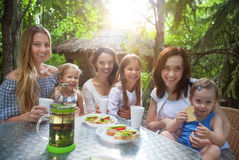 Happy mothers and her adorable little daughters at outdoors cafe Stock Images