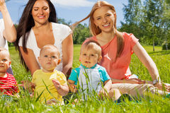 Happy mothers with their babies sitting on grass stock image