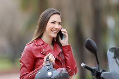 Happy motorbiker calling on phone on a motorbike Stock Photos