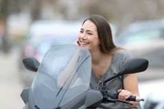 Happy motorbiker on a motorbike looking away. Happy motorbiker dreaming sitting on a motorbike looking away on the street Royalty Free Stock Images