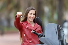 Motorcycle buyer showing keys at camera. Happy motorcycle buyer showing keys at camera outdoor royalty free stock image