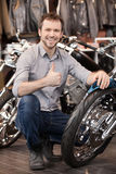 Happy motorcycle owner. Cheerful young men crouching near his ne Stock Photo
