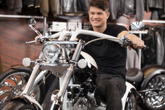 Happy motorcycle owner. Cheerful young men sitting on the motorc Royalty Free Stock Images