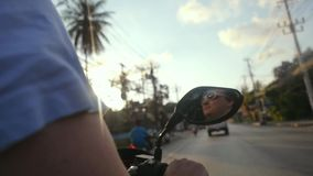 Happy motorcyclist wearing sunglasses drives motorcycle on asphalt road while traveling on tropical island during stock video