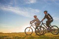 Happy mountainbike couple outdoors have fun together on a summer afternoon sunset royalty free stock images
