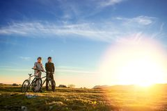 Happy mountainbike couple outdoors have fun together on a summer afternoon sunset Royalty Free Stock Photography