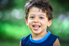 Happy mulatto boy child is smiling enjoying adopted life. Portrait of young boy in nature, park or outdoors. Concept of happy family or successful adoption or Stock Photography