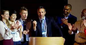Happy multi-ethnic business people applauding mature businessman on stage in seminar 4k stock video