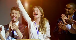 Happy multi-ethnic business people applauding young businesswoman on stage in seminar 4k stock footage