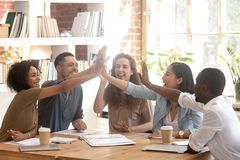Happy multi ethnic business team join hands giving high five. Happy multi ethnireative business startup team associates group join hands giving high five stock photos