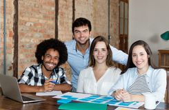 Happy multi ethnic business team looking at camera. In stylish hipster office Stock Photography