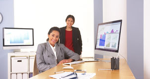Happy multi-ethnic businesswomen sitting in office royalty free stock image
