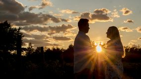 Happy multi-ethnic couple drinking wine at sunset. They stand near the vineyard. Honeymoon and travel concept