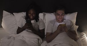 Happy multi-ethnic couple with smartphones in bed. People, technology, internet and communication concept. stock video footage