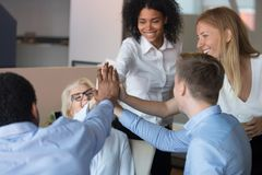 Happy employees giving high five focus on people hands. Happy multi-ethnic employees accomplish working on project celebrating unbelievable success giving high royalty free stock photography