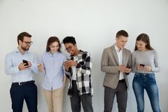 Happy multi ethnic friends or businesspeople using phones talking stock photography