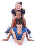 Happy multi ethnic girl friends human totem pole. Humen totem pole fun by three multi cultural teenage school student friends made up of mixed race african Stock Photography