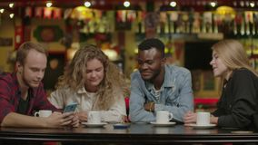 Happy multi-ethnic group of friends talking using smartphones at. Happy multi ethnic group of friends talking using. Smartphones in cafe, diverse young people stock footage