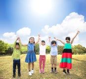 Multi-ethnic group of school children in park. Happy Multi-ethnic group of school children in park stock images