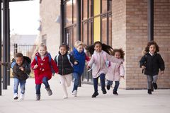 A happy multi-ethnic group of young school kids wearing coats and carrying schoolbags running in a walkway with their classmates o stock photography