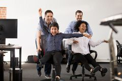 Happy multi-ethnic office people having fun riding on chairs. Diverse excited workers enjoy break together feeling free crazy on friday, happy multiracial stock images