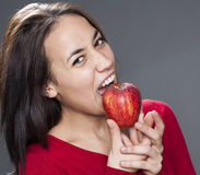 Happy multi-ethnic 20s girl eating an apple for pleasure in eating fruits Royalty Free Stock Photography