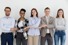 Happy multi-ethnic team people holding hands standing in row stock photography