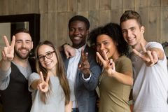 Happy multi-ethnic young people showing peace sign looking at ca. Happy multi ethnic young people looking at camera, smiling diverse friends or students showing royalty free stock photography