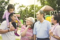 Happy multi generation family chatting in the park. Picture of happy multi generation family chatting together while standing in the park stock images